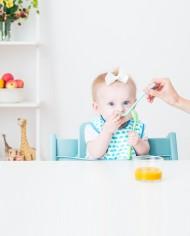 Flicka äter och håller i matningssked