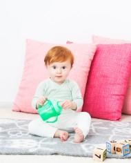 Pojke sitter på golvet med barnmugg